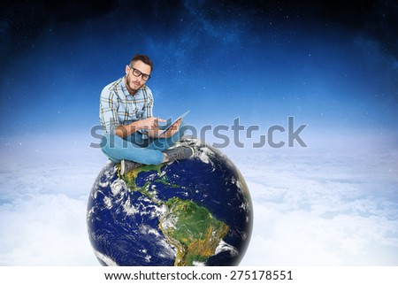 Handsome hipster using tablet pc against white clouds under blue sky - stock photo