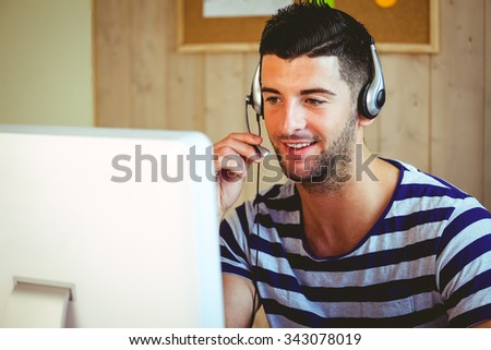 Handsome hipster working at desk in his office