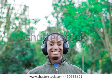 Handsome hispanic black man wearing green sweater in outdoors park area, headphones on covering ears and smiling enjoying some music - stock photo