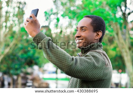 Handsome hispanic black man wearing green sweater in outdoors park area holding up phone and watching screen as in taking selfie - stock photo