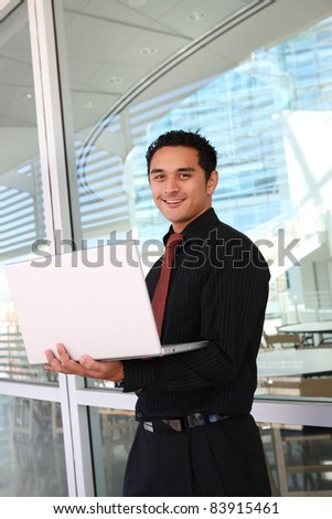 Handsome hispanic business man at office with laptop computer - stock photo