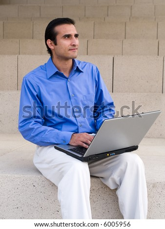 Handsome hispanic businessman surfing the internet on a laptop while sitting on steps outside an office building.