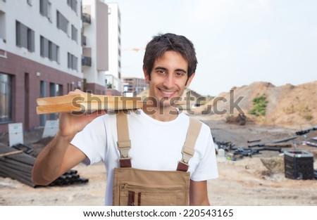 Handsome hispanic carpenter laughing at camera - stock photo