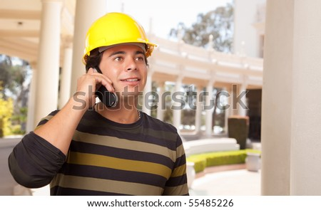 Handsome Hispanic Contractor with Hard Hat Talking on His Cell Phone. - stock photo