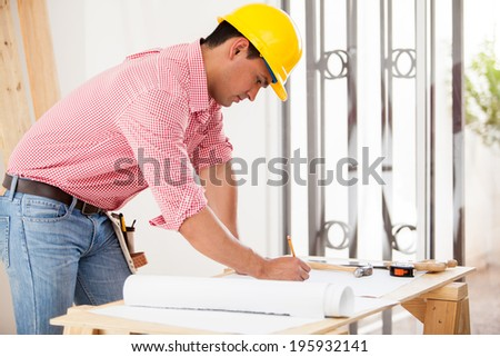 Handsome Hispanic engineer doing some design work and remodeling a house - stock photo