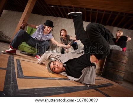 Handsome Hispanic male break dancer spinning on back - stock photo