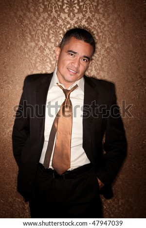 Handsome Hispanic man in suit against gold wallpaper background - stock photo