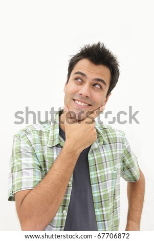 handsome hispanic man looking upwards at copyspace thinking - stock photo