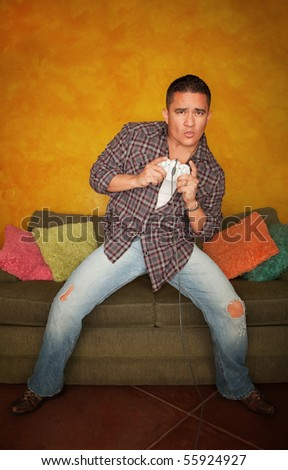 Handsome Hispanic man playing Video game - stock photo