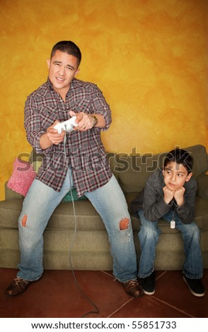 Handsome Hispanic man playing Video game with bored young boy - stock photo