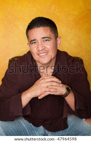 Handsome Hispanic Man Seated in Colorful Chair - stock photo