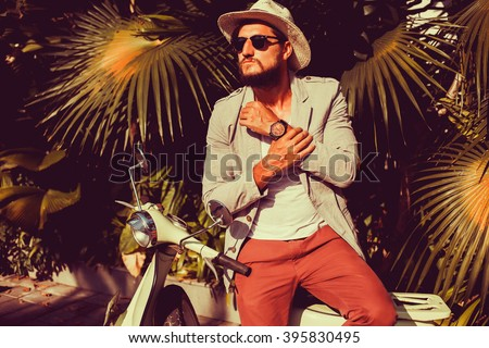 handsome in a light jacket, hat and red trousers, sunglasses with mustache and beard about posing retro scooter, fashionable clothes, brutal man, stylish outfit,walk down the street, watch  - stock photo