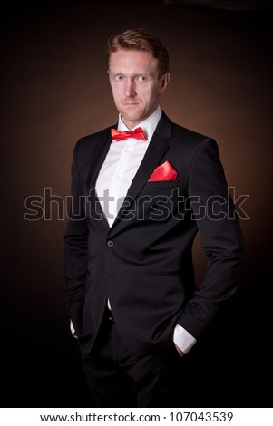 handsome in  tuxedo with red bow - stock photo