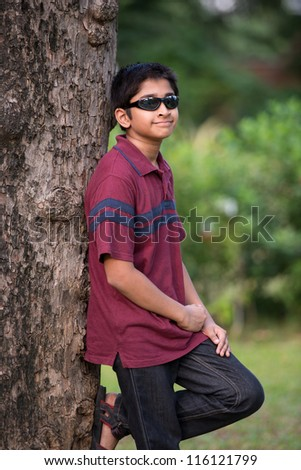 Handsome Indian boy standing outdoor smiling - stock photo
