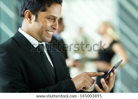 handsome indian business executive working on tablet computer in office - stock photo