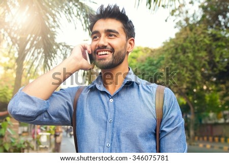 Handsome Indian guy talking on his smart phone with smile on his face - stock photo