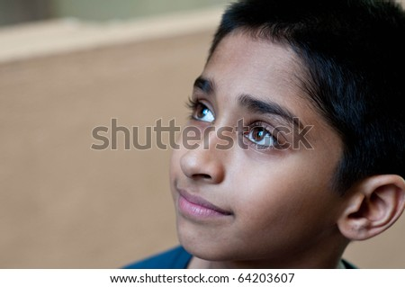 handsome indian kid day dreaming - stock photo