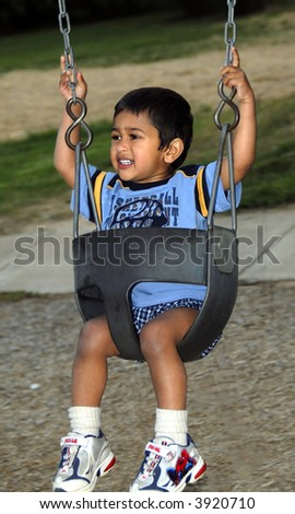 Handsome Indian kid having fun with the swing - stock photo