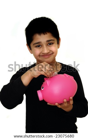 Handsome Indian kid saving money in a piggy bank - stock photo
