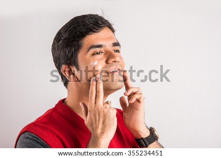 Handsome indian man applying sunscreen on his face, asian man applying face cream, Young indian man with moisturiser on the face, asian man and moisturiser or moisturizer on face, indian man & facial - stock photo