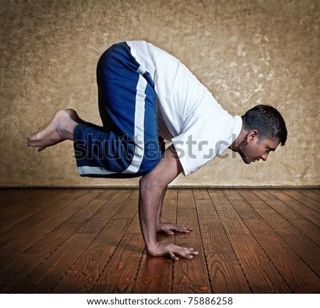 Handsome Indian man in white shirt doing bakasana, crane pose indoors on wooden floor at grunge background - stock photo