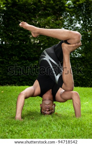 Handsome Indian man practicing yoga outside. - stock photo