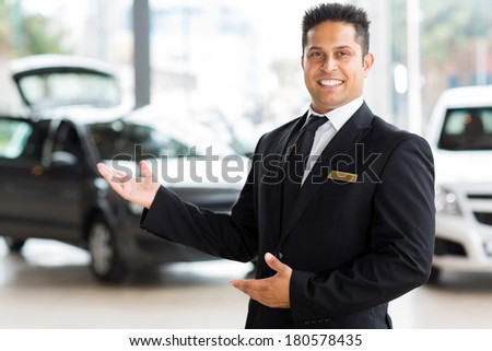 handsome indian salesman presenting new car to clients