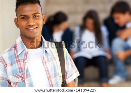 handsome indian teenage high school student carrying schoolbag - stock photo