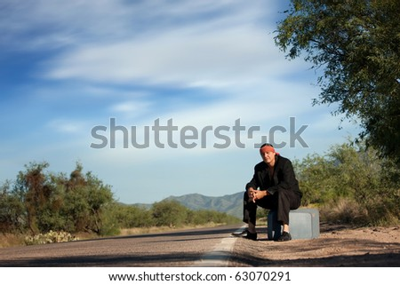 Handsome indigenous man by the side of the road with copy space - stock photo