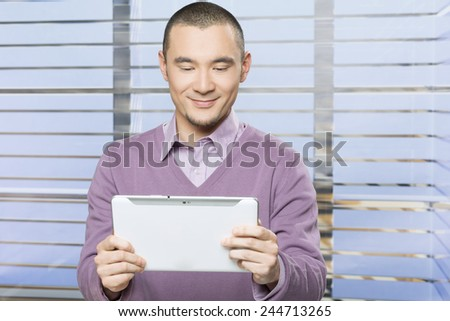Handsome Japanese businessmen in the office checking emails on his tablet pc  - stock photo