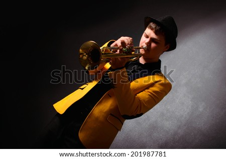Handsome jazz trumpet player in hat and yellow jacket playing trumpet. Portrait of young musician playing the trumpet at studio. - stock photo