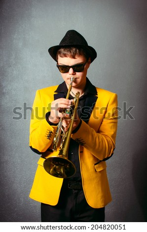 Handsome jazz trumpet player in hat, yellow jacket and black glasses playing trumpet. Portrait of young musician playing the trumpet at studio. - stock photo