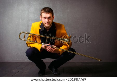 Handsome jazzer man with trombone in yellow jacket. Portrait of brutal young musician holding trombone posing in studio - stock photo