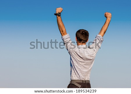 Handsome joyful businessman businessman raising his arms upwards show the victory to the world