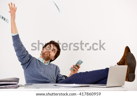 Handsome joyful young businessman sitting at the office desk with feet on the desk throwing money over his head. Looking away. Isolated on white background. - stock photo