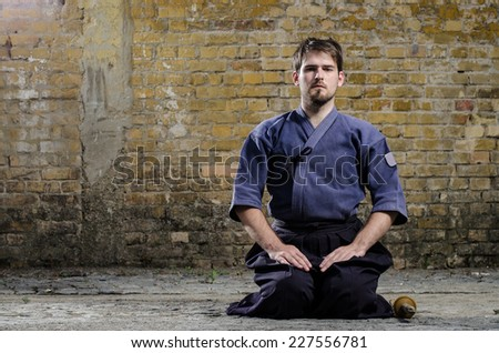 Handsome kendo warrior posing against old brick wall. - stock photo