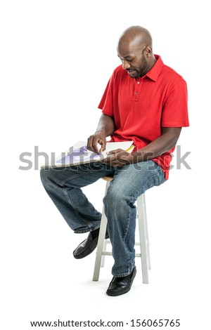 Handsome late 20s black man artist drawing a picture with pastels on a sketch pad isolated on white background