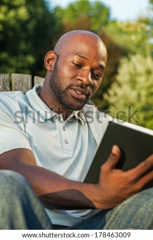 Handsome late 20s black man relaxing reading a book at the park in summer