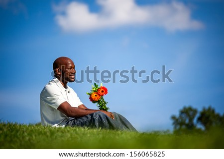 Handsome late 20s black man waiting for his date with a bouquet of flowers at the park on a sunny summer day - stock photo