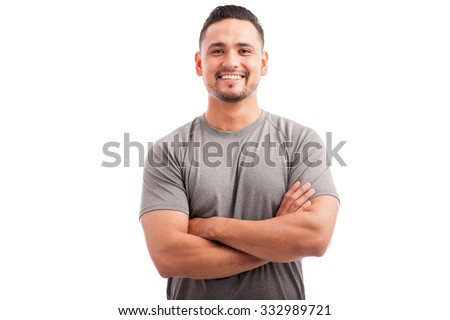 Handsome Latin athlete in a sporty outfit with his arms crossed and smiling on a white background - stock photo