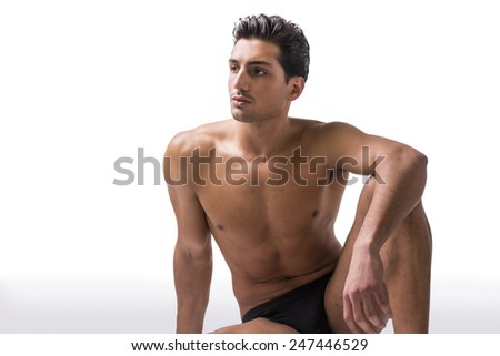 Handsome latin young man sitting naked on floor, wearing only underwear. Muscular build - stock photo