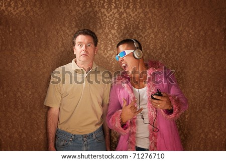 Handsome Latino guy listening to music while his friend is petrified - stock photo