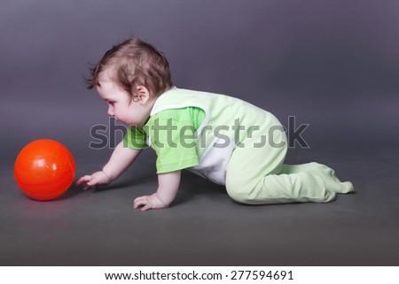 Handsome little baby boy in green crawls on floor for ball in grey studio - stock photo