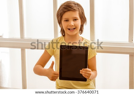 Handsome little boy holding a tablet, showing OK sign, looking in camera and smiling while sitting near the window - stock photo