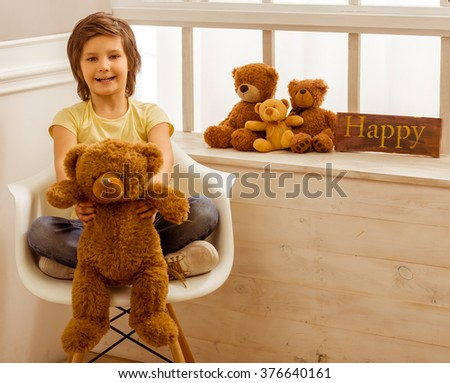 Handsome little boy holding a teddy bear looking in camera and smiling while sitting on a chair near the window - stock photo