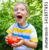 Handsome little boy holding tomato in green garden - stock photo