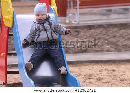 Handsome little boy in grey rides in slide and smiles on playground at spring day - stock photo