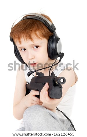 handsome little boy in headphones playing with the pistol - stock photo