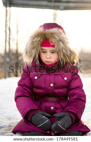 handsome little boy in winter clothes sitting alone offended and sad - stock photo