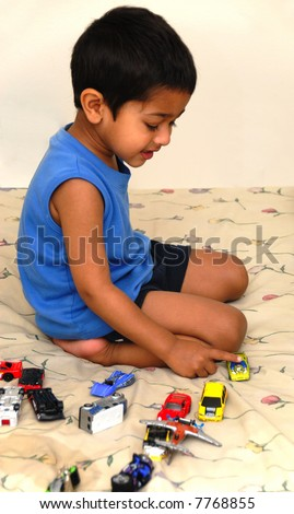 Handsome little boy playing with toy car in bed - stock photo